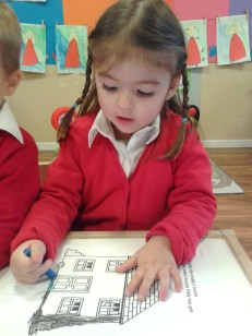 girl in pigtails coloring house