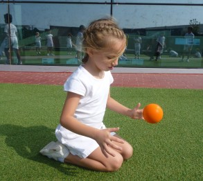 girl bouncing orange ball