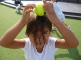 girl with tennis ball on head